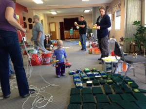 Members of Highlands United Methodist Church in Denver assemble cleaning buckets for those affected by the Colorado floods, while toddler Emma, daughter of two of the volunteers (not pictured) plays amid the cleaning supplies. A UMNS photo by the Rev. Bradley Laurvick.