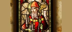 A stained-glass window in the United States depicts St. Patrick with his staff and holding a church.