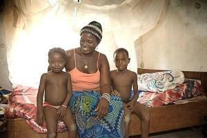 Habibatu Fugbawa sits with two of her children in front of the insecticide-treated mosquito net she received in 2010 from the United Methodist Church's Imagine No Malaria campaign at her home in Bumpe, Sierra Leone.