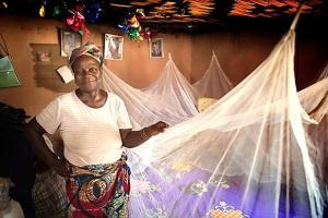 Matilda Ndanema displays the insecticide-treated mosquito net she received from the United Methodist Church's Imagine No Malaria campaign in 2010 at her home in Bumpe, near Bo, Sierra Leone.