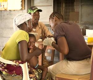 Health worker Juliana Koroma (right) takes a blood sample from Issata Jusu for a malaria test at the Koribondo Community Health Center near Bo, Sierra Leone. Holding the child is her is her mother, Umu Koroma. At rear is health worker Ishmael Karoma.